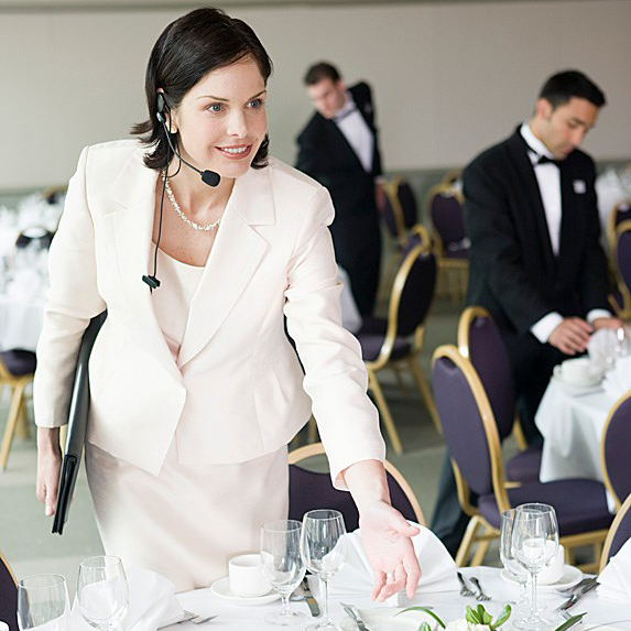 A wedding planner in a suit looks over a table in preparation for a wedding.