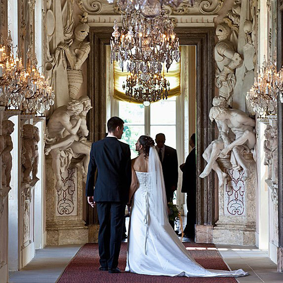 A couple walks down the aisle in a hall with statues and a chandelier
