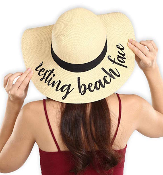 "Model has her back to the camera as she shows off the embroidered message of ""resting beach face"" on her straw beach hat"