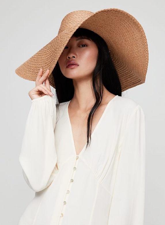 Model wears an oversized large-brimmed straw hat