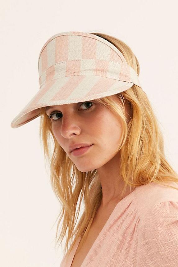 Model wears striped sun visor hat