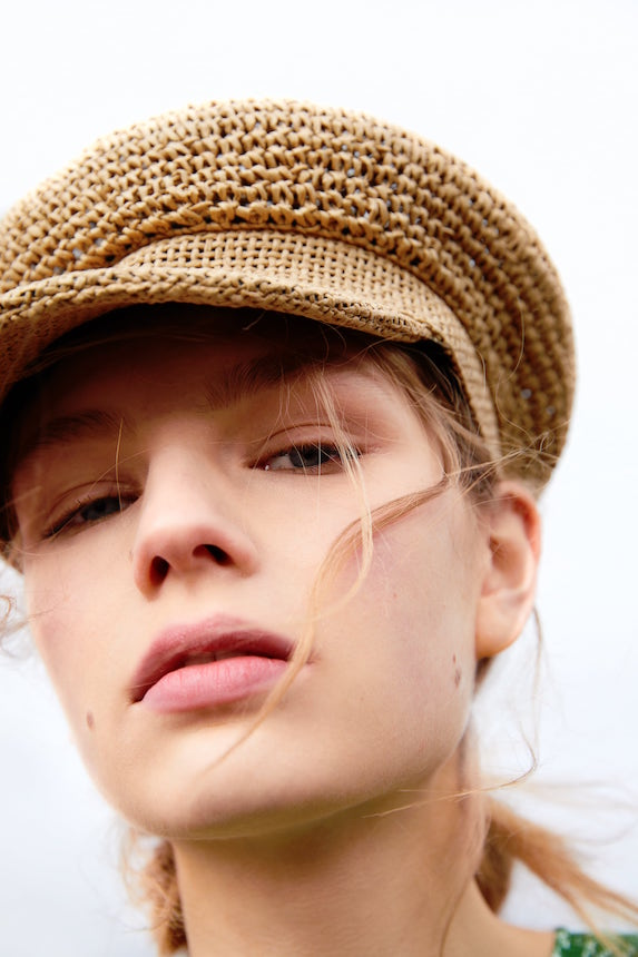 Model wears natural-coloured straw hat in a baker boy cap
