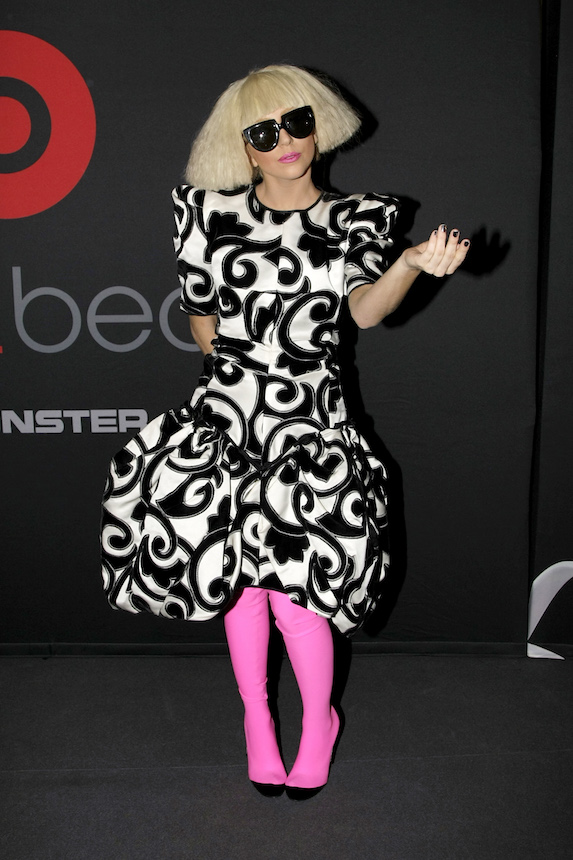 Lady Gaga wears a black and white dress with neon pink stocking-style boots and styles her hair in a choppy blonde style with black sunglasses