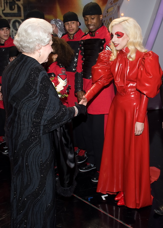 Lady Gaga wears a red latex ensemble as she greets the Queen of England in 2009
