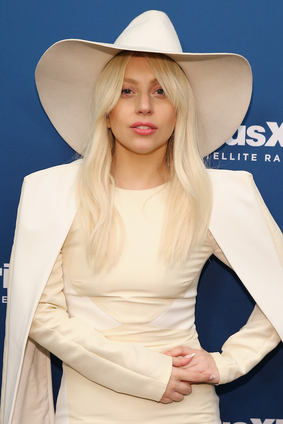 Lady Gaga wears a monochromatic off-white outfit and hat to a radio event in 2013