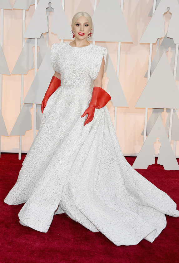 Lady Gaga wears a custom white gown and red elbow-length gloves to the 87th Academy Awards in 2015