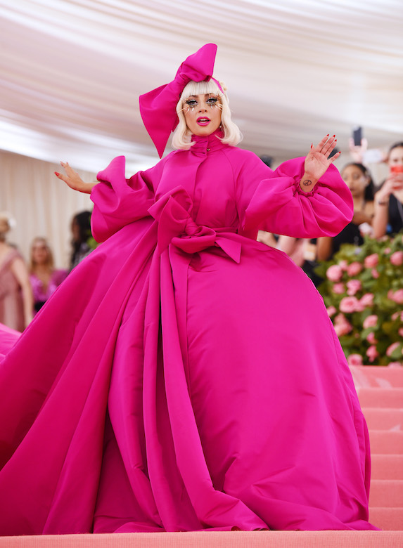 Lady Gaga in a pink ensemble while in character performing on the red carpet of the 2019 Met Gala