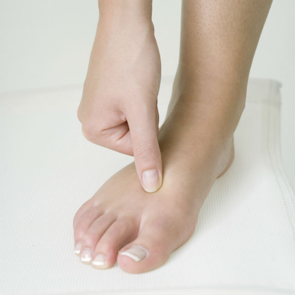 Woman's thumb pressing into top of the foot, just below the big toe