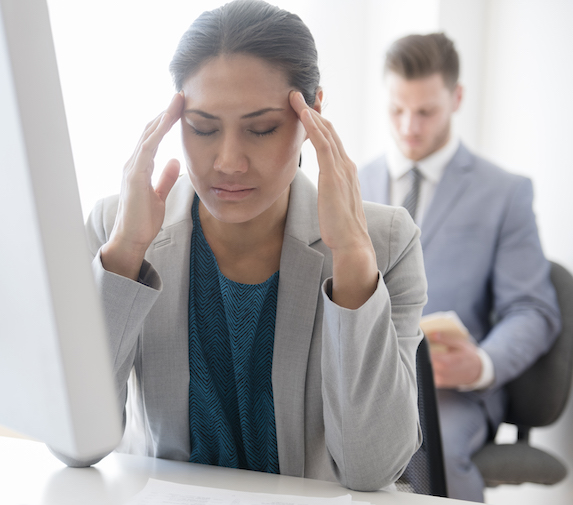 Woman rubs her temples in frustration at work