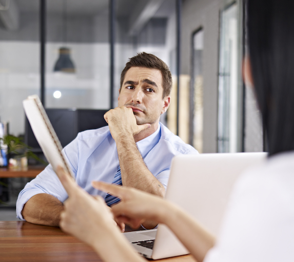 Man looks deep in though while looking at his female coworker