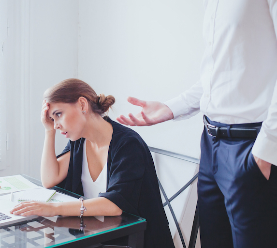 Frustrated woman sits at a desk while her male coworker stands behind her