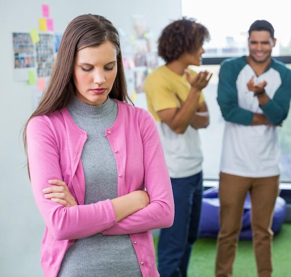 Woman looks insecure as coworkers gossip behind her