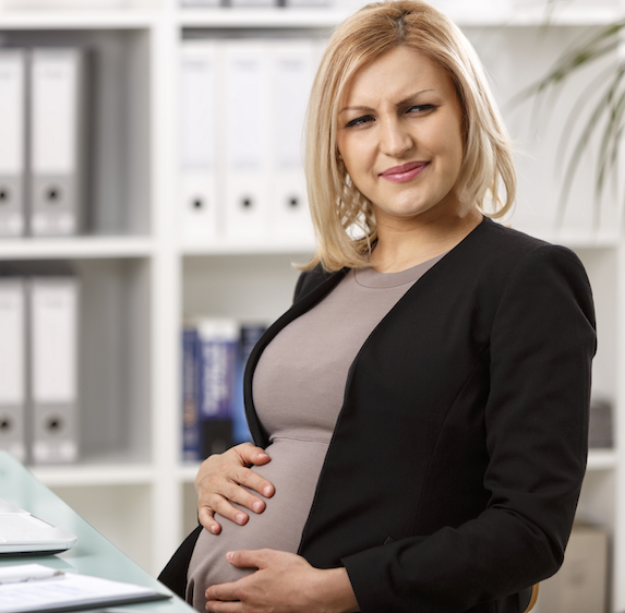 Pregnant woman looks annoyed at work