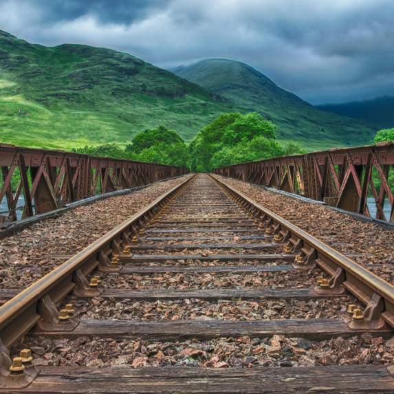 empty train tracks with mountain range in the distance