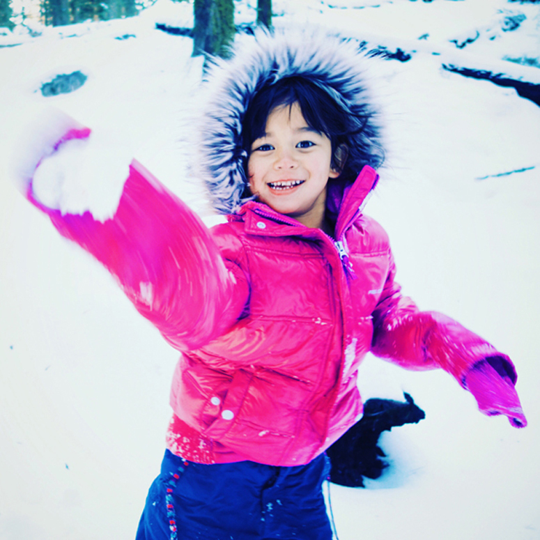 a young girl in a bright pink parka throwing a snowball