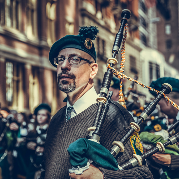 a middle age man in traditional tartan, holding bag pipes on a busy city street