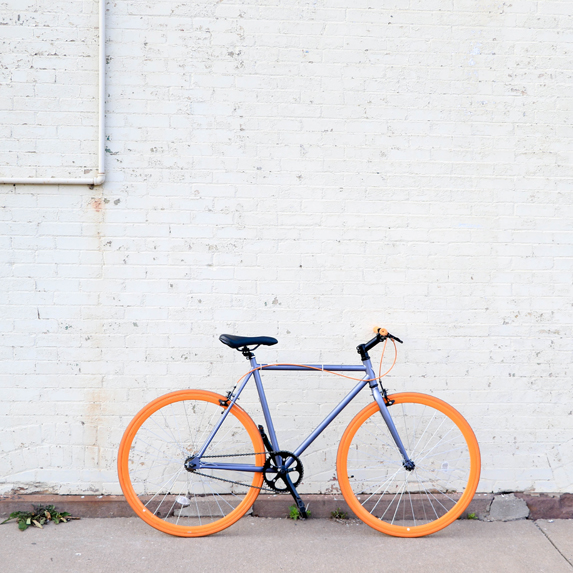 a bicycle leaning against a white brick wall
