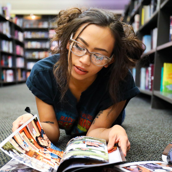 a girl flipping through comic books at the library