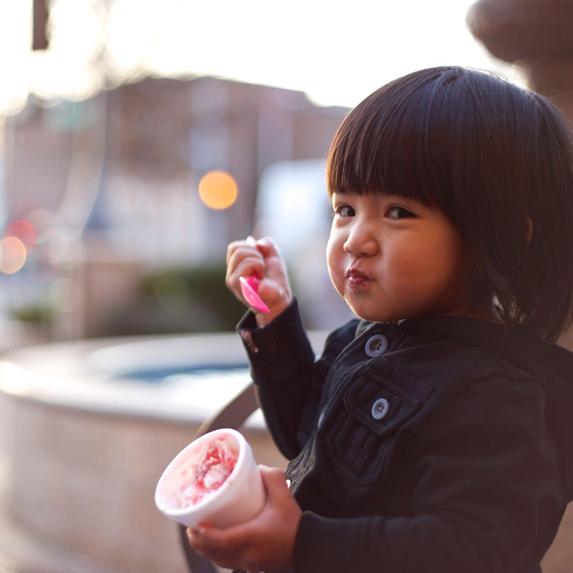 a toddler enjoying ice cream on a city street