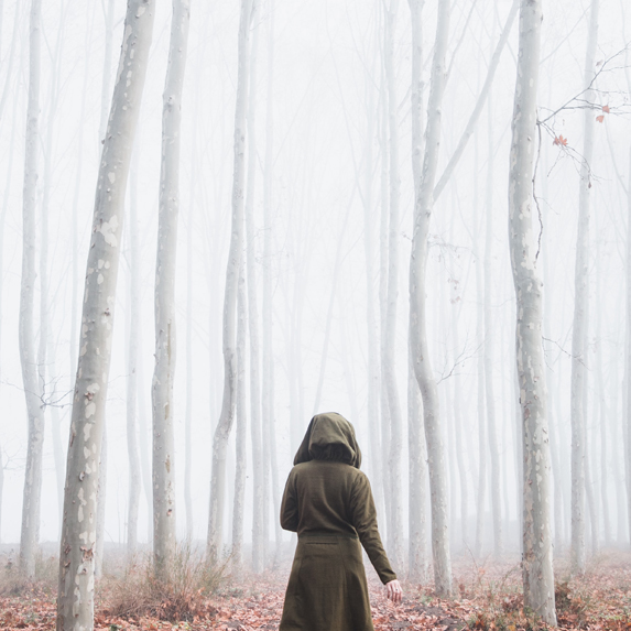 a woman wearing a hood walking into the woods