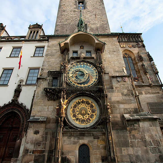 The astronomical clock as seen in the daytime, with two large clock faces and golden dials, surrounded by brown stone buildings