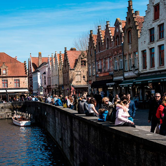 Tourists walking along the streets of Bruges, alongside the canal
