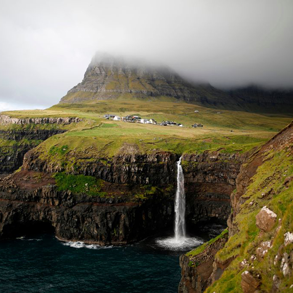 The Gásadalur village, on top of grass-covered cliffs, with a misty mountain in the background and a waterfall that feeds into the ocean