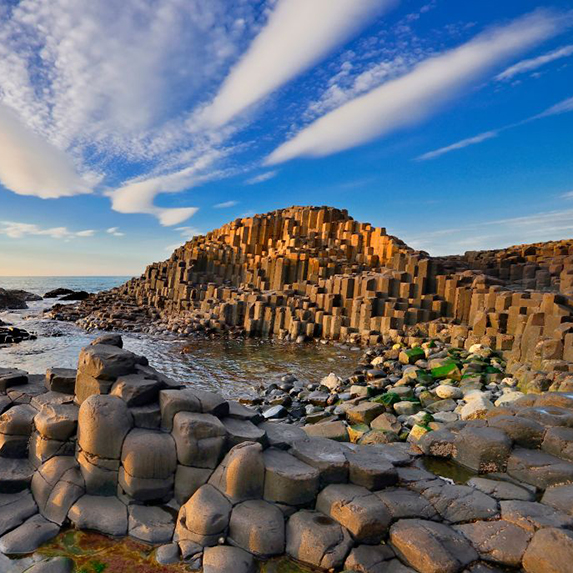 Thousands of column-shaped rocks made from lava make up the Giant's Causeway, as seen here on a clear day at sunset