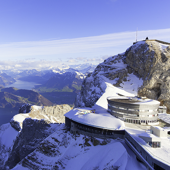 A snow-covered Mount Pilatus, a mountain in the Swiss Alps, overlooking lakes and rocky peaks