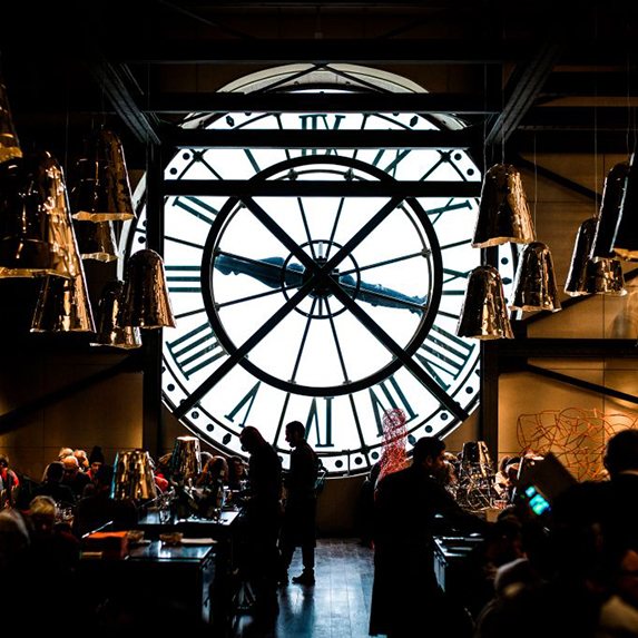 The iconic clock window as seen in silhouette with tourists milling around in front, in the Musée d'Orsay