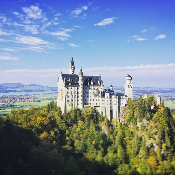 The white limestone walls and blue turrets of Neuschwanstein Castle are seen from a distance, surrounded by green forest and blue sky