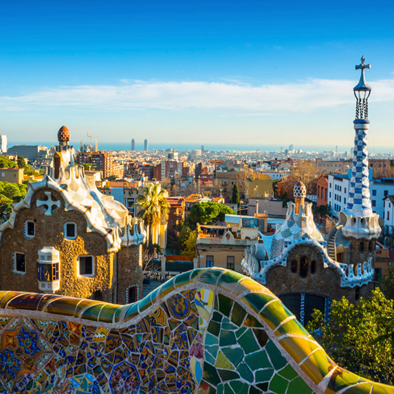 Park Guell's iconic mosaic-tiled bench on the terrace, overlooking a blue sky and the Barcelona skyline