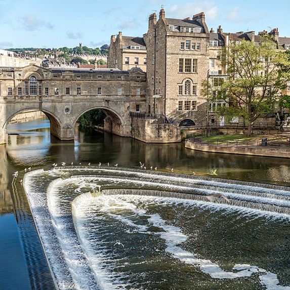 Pulteney Bridge is seen on a sunny day with waves in its water feature on the river below and honey-coloured stone buildings