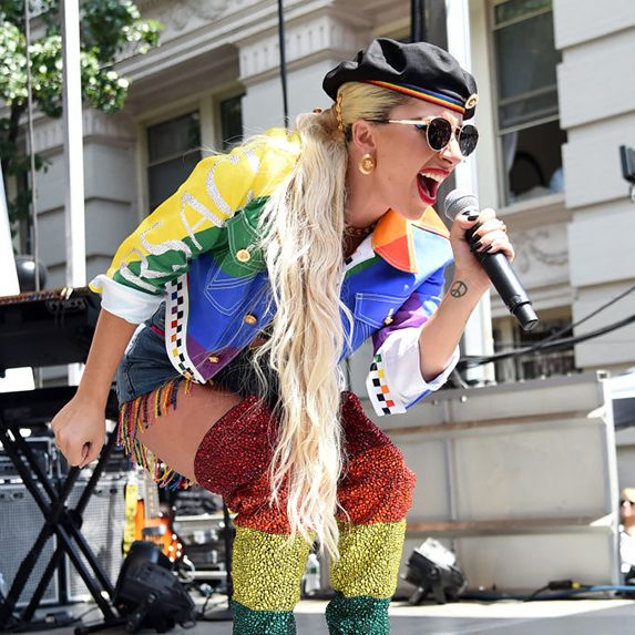 Lady Gaga performing onstage in a rainbow suit, with a long blonde ponytail and dark glasses