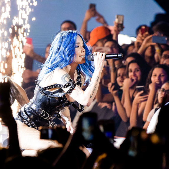 Halsey performs with fireworks going off behind her, in a bright blue wig and black dress