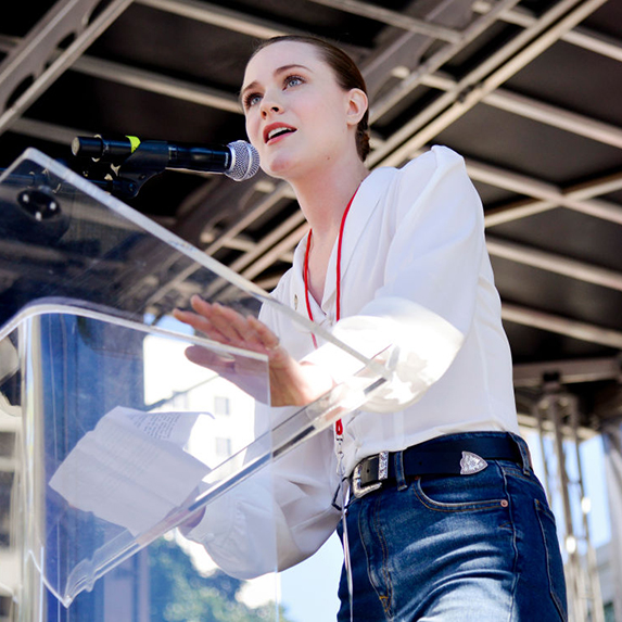Evan Rachel Wood speaks at a podium in a white long sleeve shirt, with her brown hair tied back in a bun