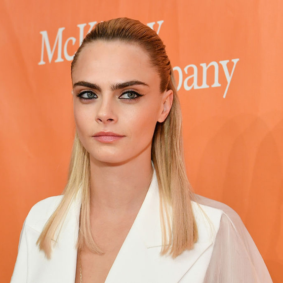 Cara Delevingne poses with her long blonde hair half-up, in a white long sleeve shirt
