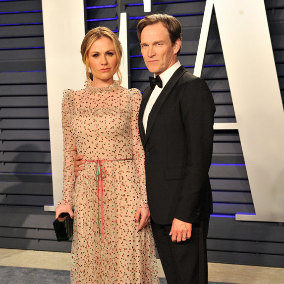 Anna Paquin poses in a long, sheer beige dress with her husband Stephen Moyer, in a black suit