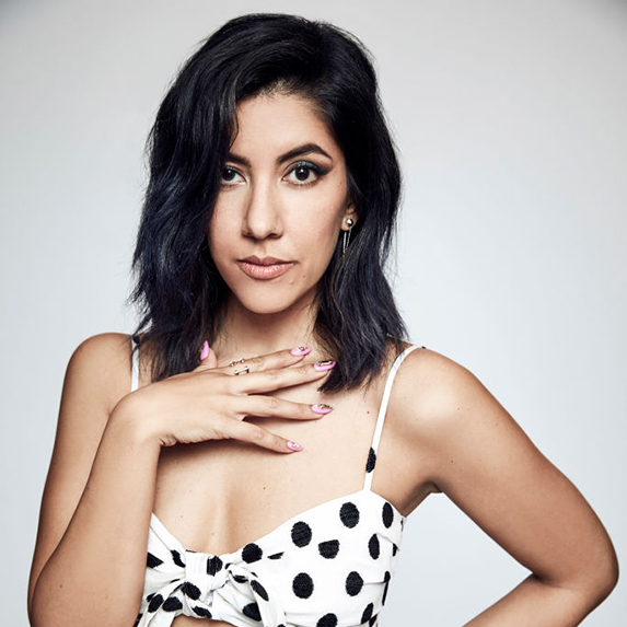 Stephanie Beatriz poses with her black hair down, in a white and black polka-dot top