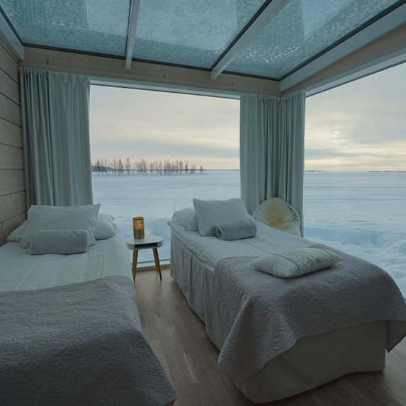 The view from inside a glass villa in Lapland, showing snow-covered fields outside the window