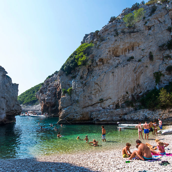 Beachgoers relax on the sand at Stiniva Beach on a sunny day, with turquoise waters and two cliffs on either side of the cove