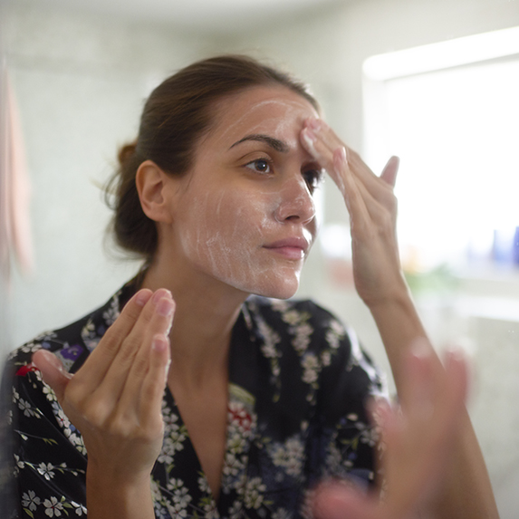Woman applies coconut oil on forehead