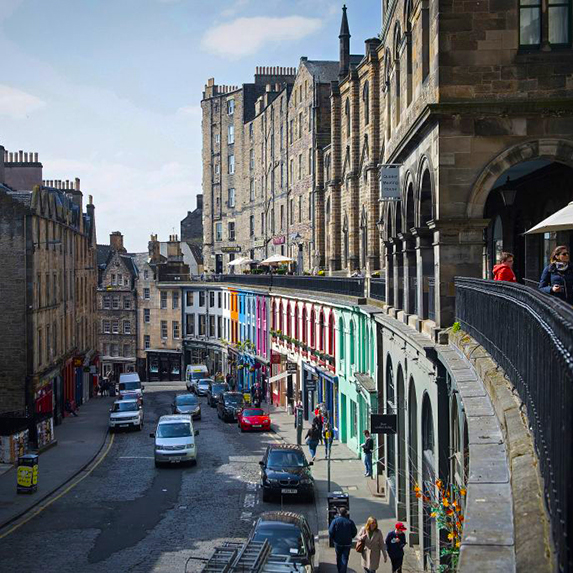 A view from the top of Victoria Street in Edinburgh, showing the curve of the street and its multicoloured storefronts