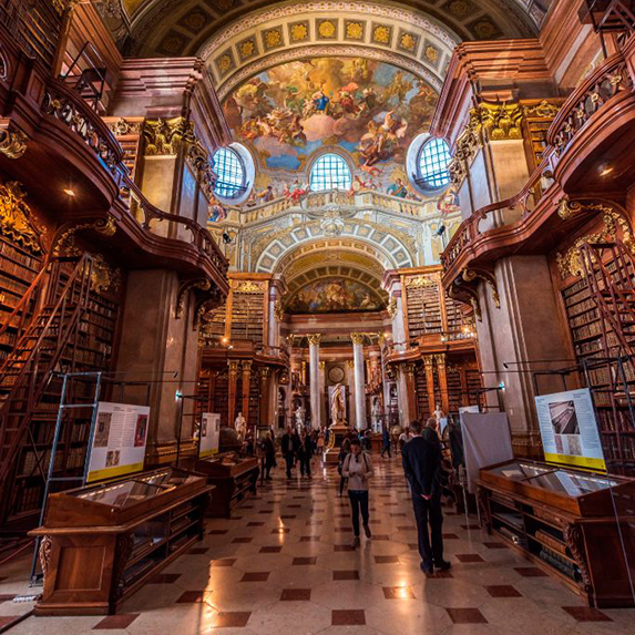 The Austrian National Library, with black and white marble floors, gleaming wooden bookshelves and ladders, and painted ceilings