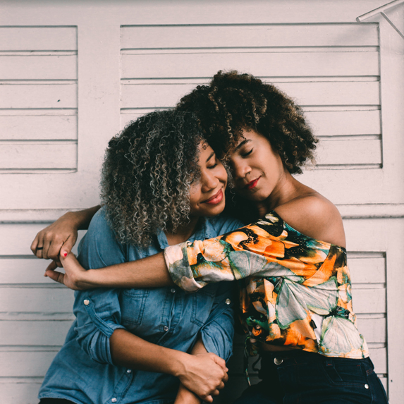 Two friends embracing one another in front of a house