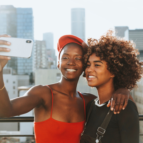 Two young women posing for a selfie outdoors in the city
