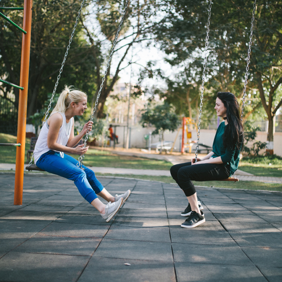 Two young women on swings in a playground, facing one another