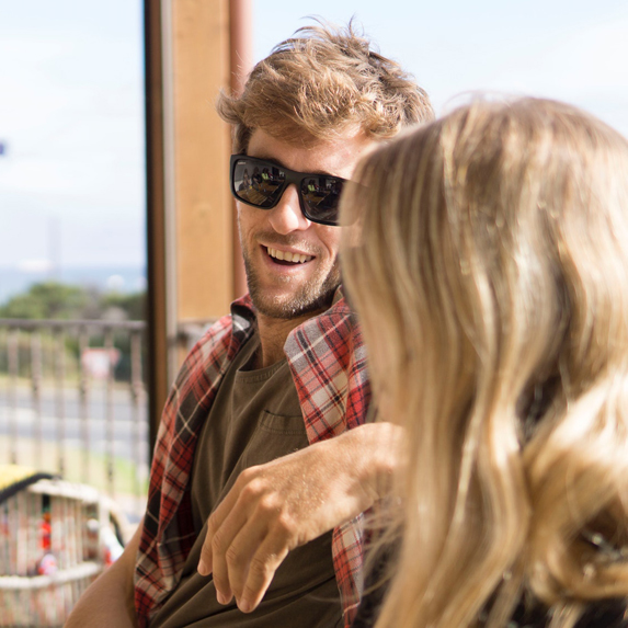 A man and woman chatting on the patio of a pub or restaurant