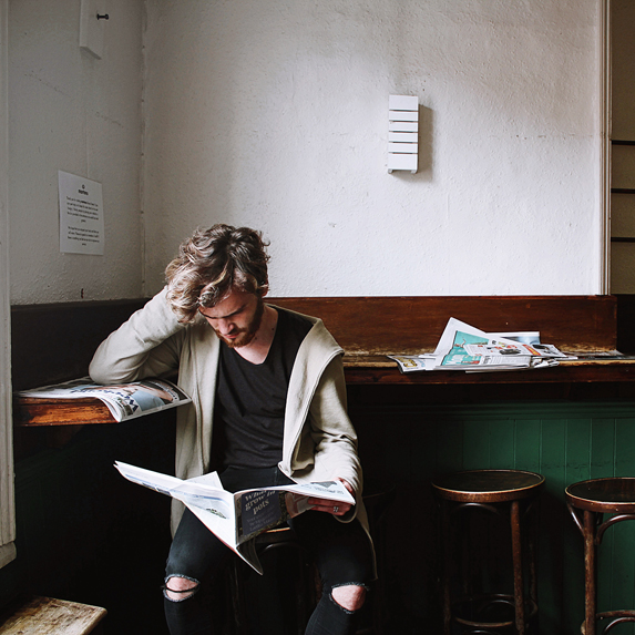 A young man reading newspapers in a rustic coffee shop