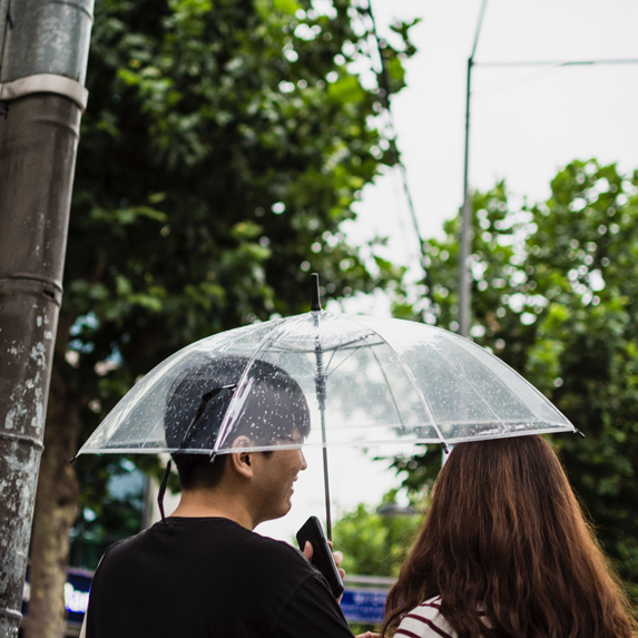 A young couple laughing together under an umbrella in the rain